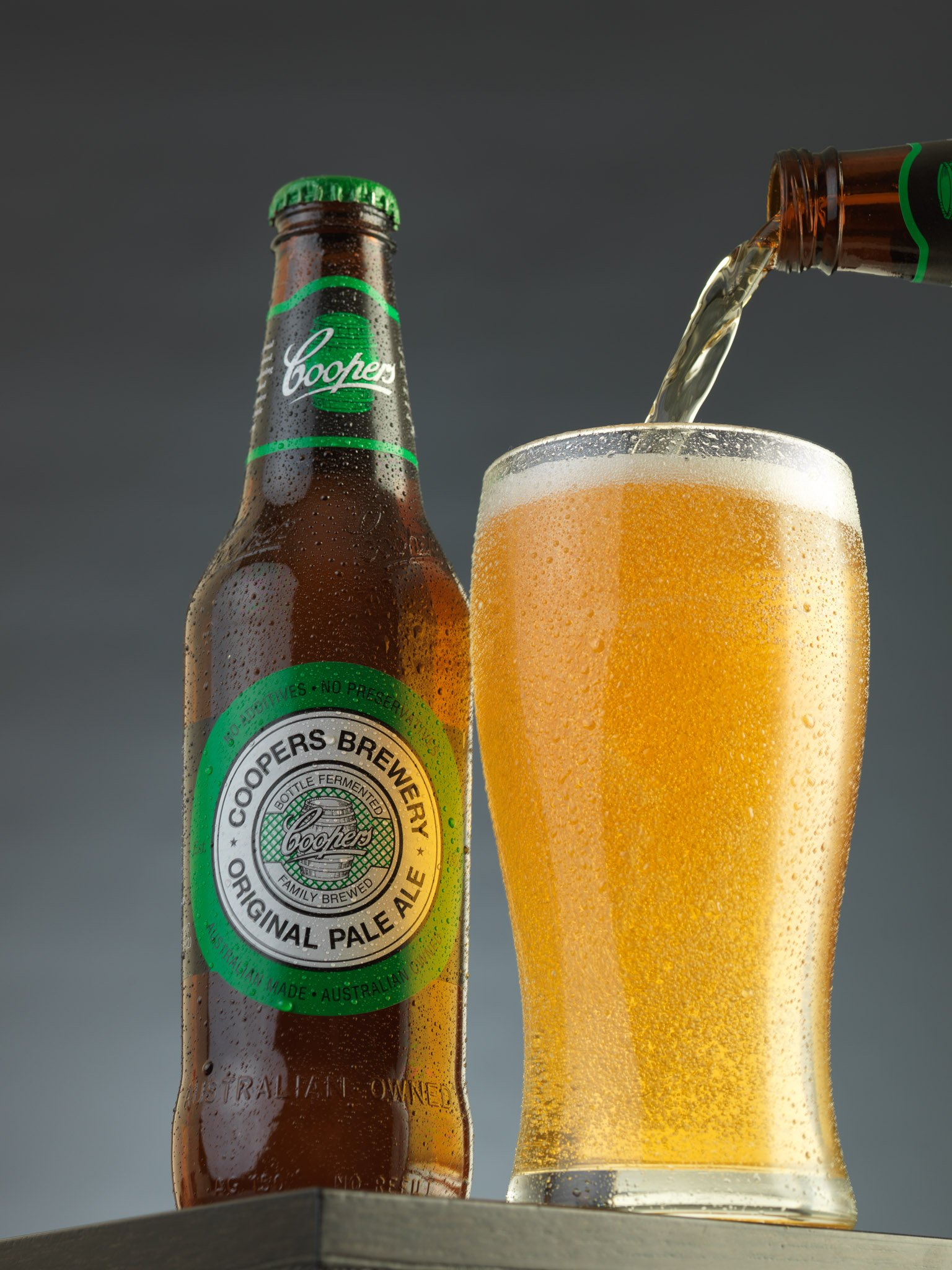 Glass of Coopers Pale Ale being poured, with a full bottle beside