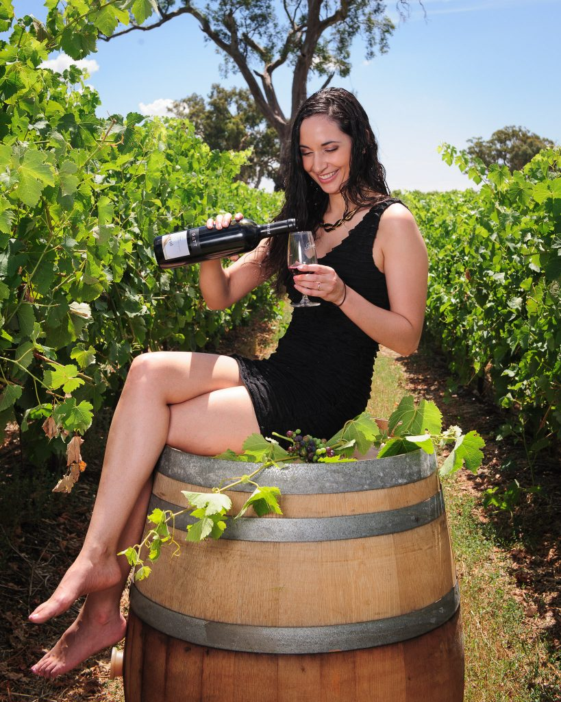Girl pouring wine from a bottle seated on a winebarrel in a vineyard
