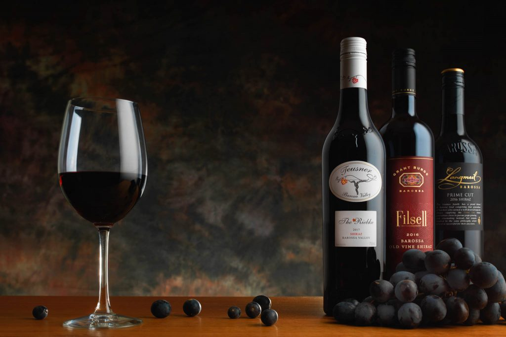 Wine bottle photography showing a set of three bottles of shiraz wine with wineglass and grapes